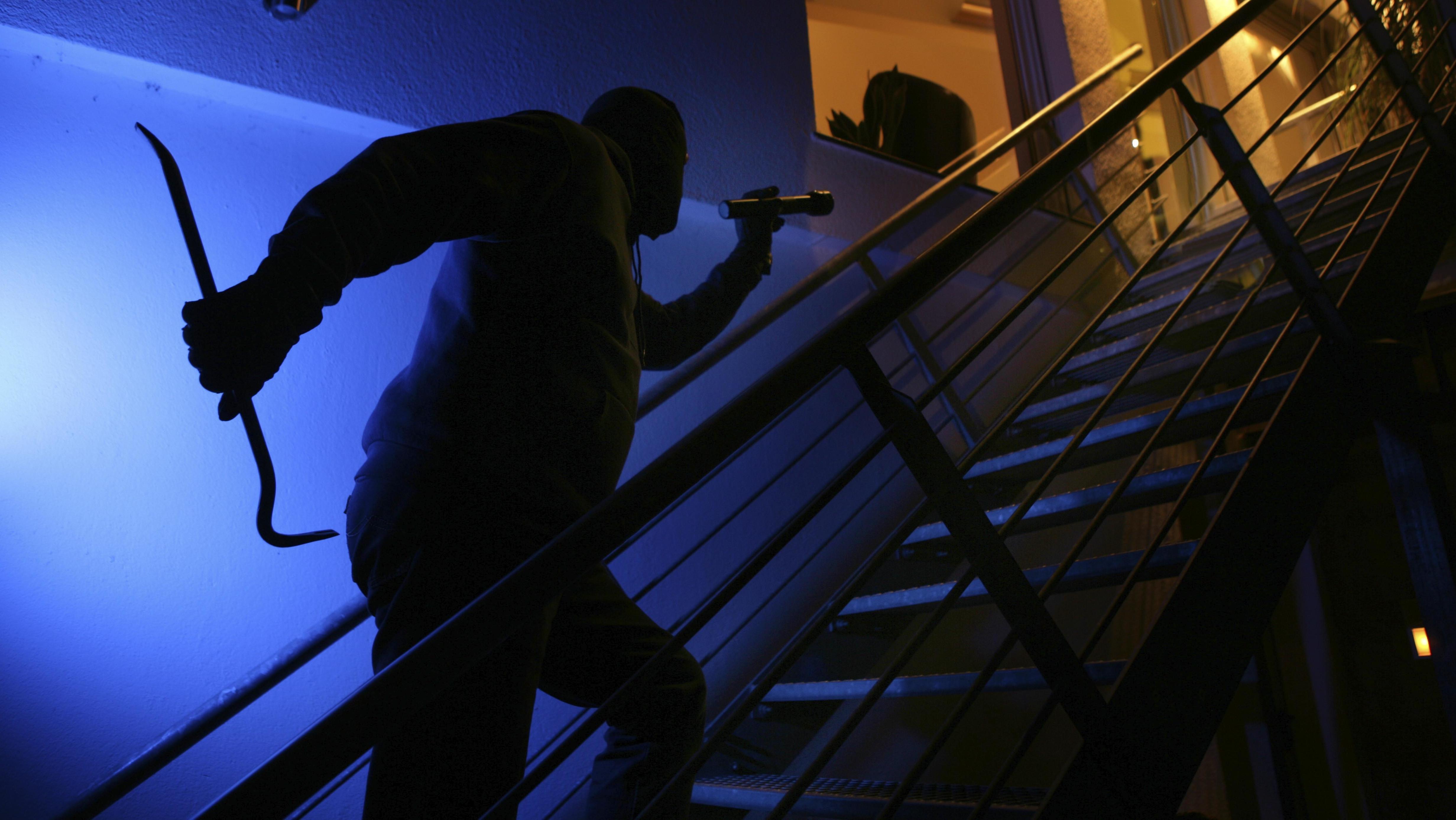 Ein Einbrecher mit Brecheisen steigt im Schutz der Dunkelheit die Außentreppe eines Wohnhauses hinauf; in den Räumen brennt Licht.