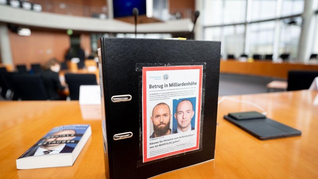 Aktenordner mit Fahndungsfotos des früheren Wirecard-Finanzvorstands Jan Marsalek ist im Sitzungssaal zum Bilanzskandal Wirecard  zu sehen.