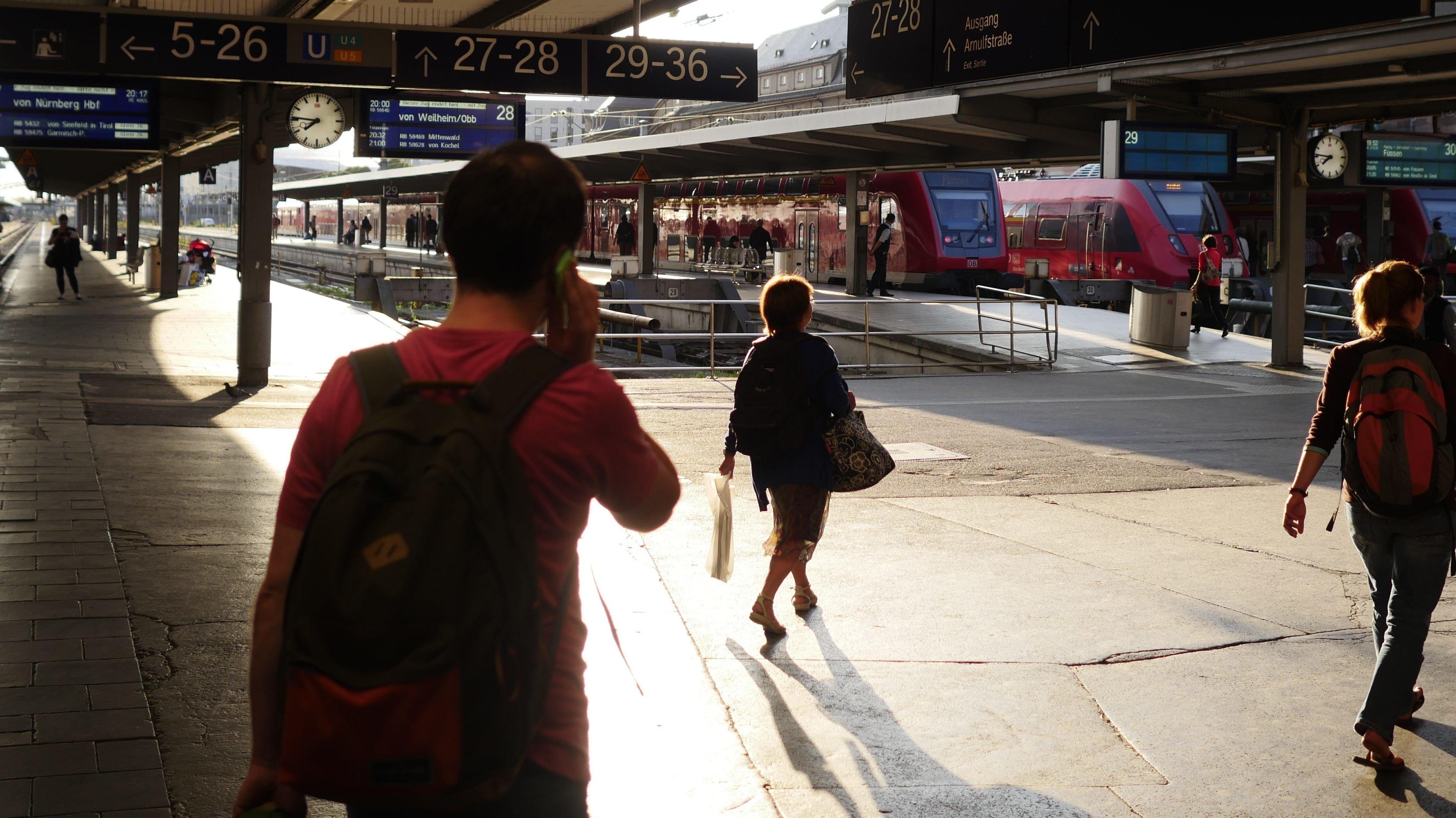 Mensch mit Handy an den Bahngleisen  Hauptbahnhof