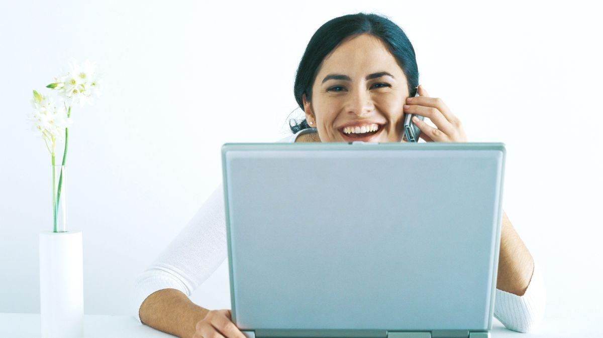 Lachende Frau hinter einem Laptop