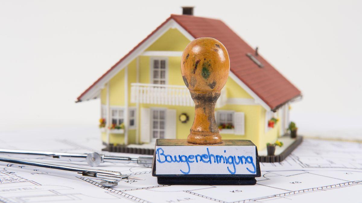 Symbolfoto mit Modellhaus und Geodreieck zum Thema Baugenehmigung