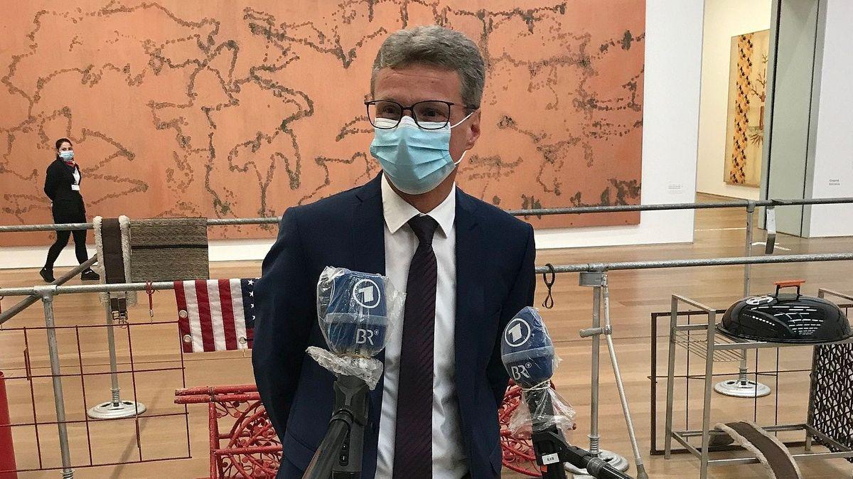 Kunstminister Bernd Sibler mit Mundschutz auf der Pressekonferenz im Museum Brandhorst, vor ihm BR-Mikrofonen mit Schutzfolie, hinter ihm eine Absperrung und ein großes Wandgemälde