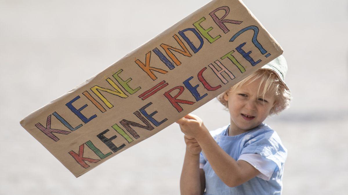 Ein kleines Mädchen mit einem großen Plakat, auf dem die Frage steht: Kleine Kinder, Keline Rechte?