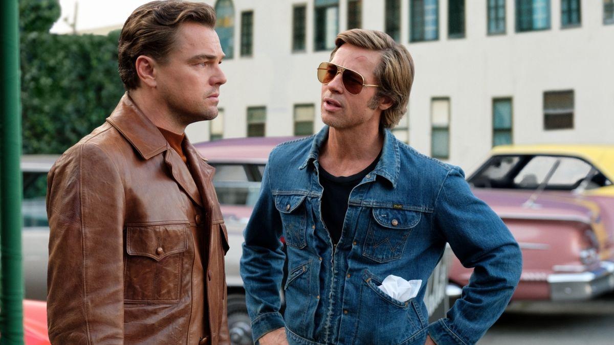 """Leonardo DiCaprio und Brad Pitt stehen auf einem Parkplatz nebeneinander (Szenenfoto aus """"Once Upon a Time in Hollywood"""" von Quentin Tarantino)"""