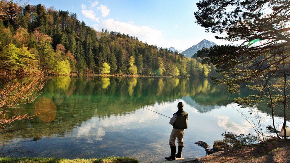 Ein Angler steht am Alatsee bei Füssen