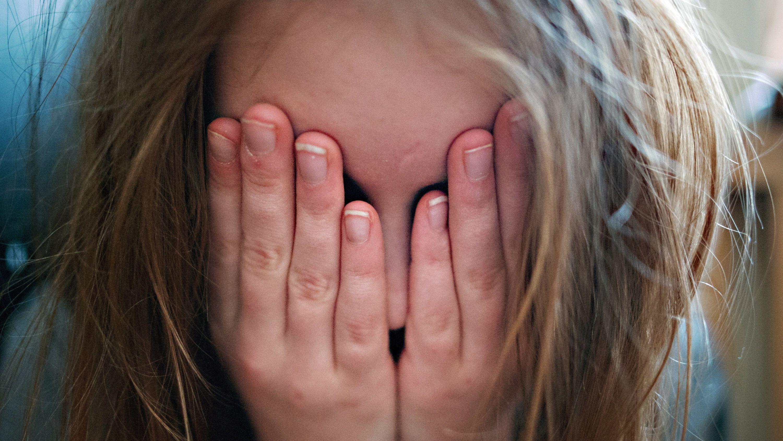 Ein junges Mädchen hält sich die Hände vor ihr Gesicht