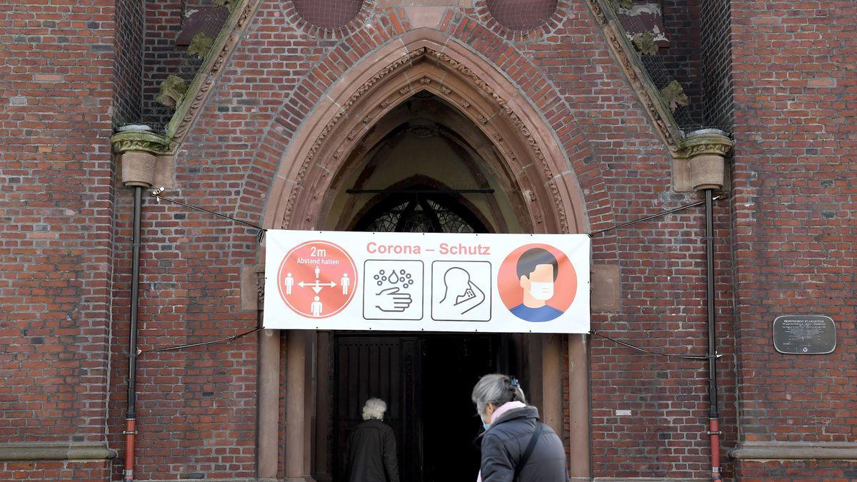 Ein Banner mit Informationen zum Schutz vor Corona-Infektionen hängt über dem Eingangsportal einer Kirche.