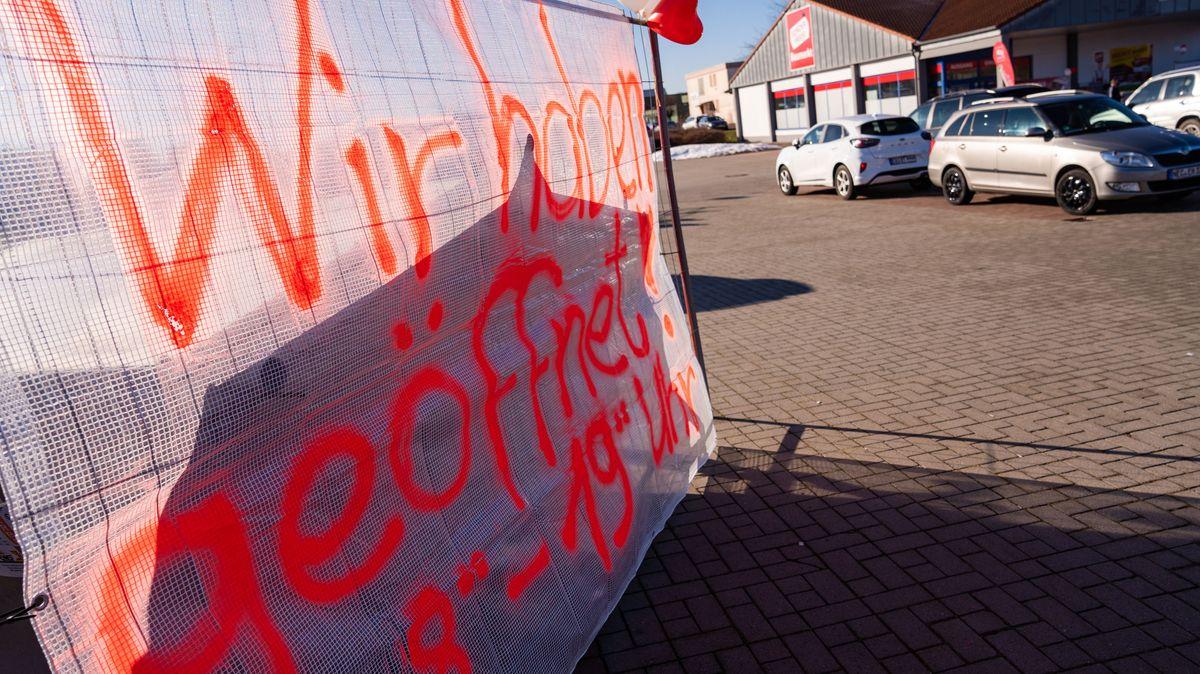 """Auf dem Parkplatz eines Baumarktes steht ein Schild mit der Aufschrift """"Wir haben geöffnet""""."""