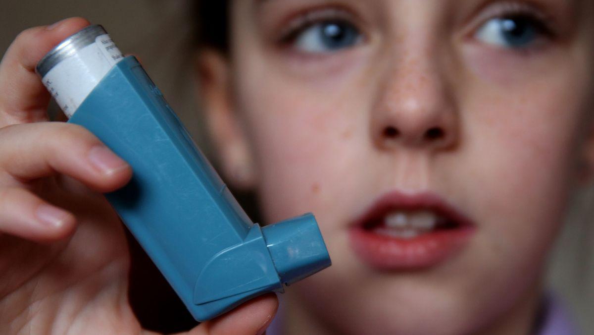 Kind mit Asthma-Spray in der Hand.