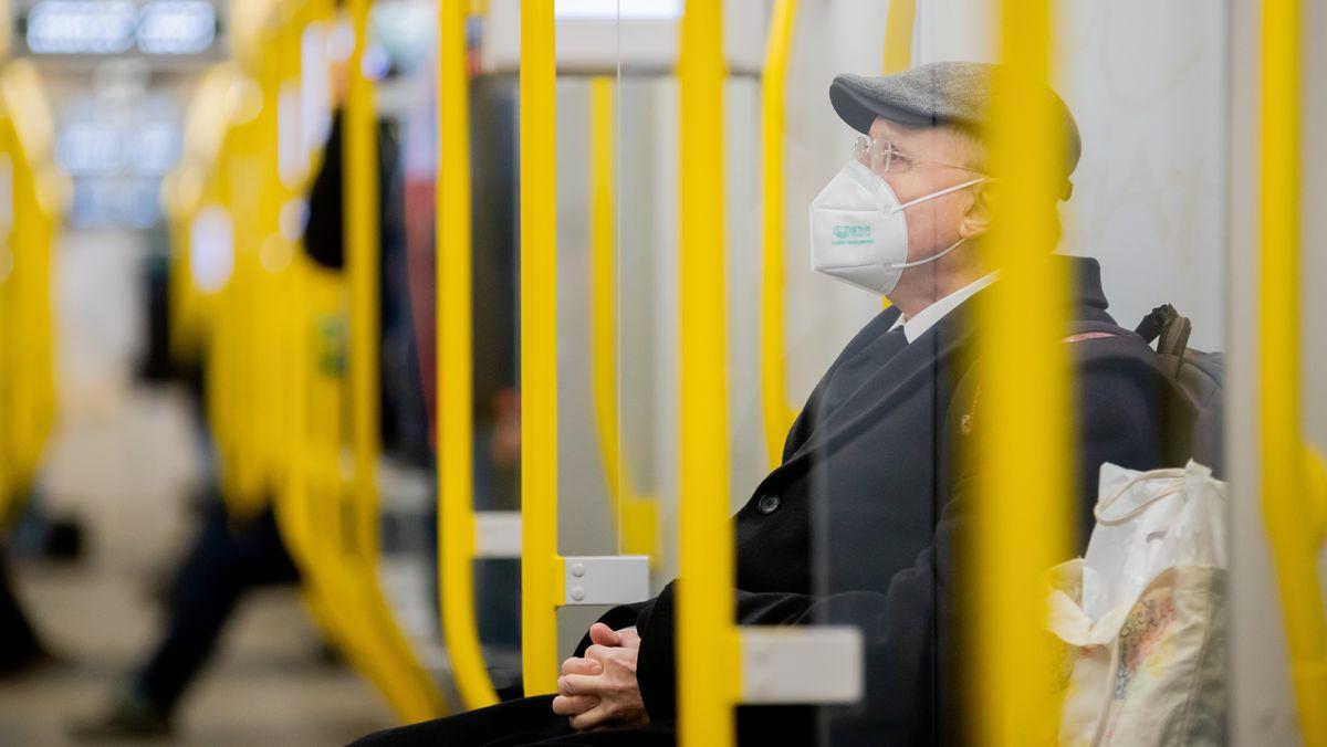 Ein Mann sitzt mit FFP2-Maske in der U-Bahn. In Deutschland müssen im ÖPNV sowie beim Einkaufen FFP2-Masken oder OP-Masken getragen werden.