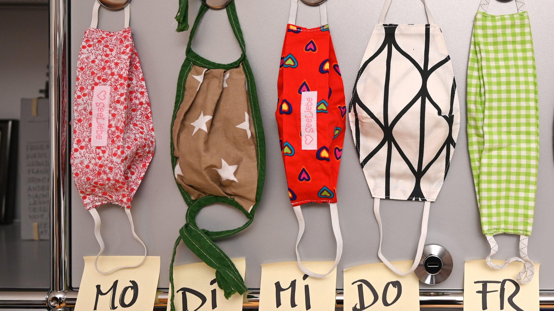 Fünf selbstgebastelte Gesichtsmasken, aufgehängt an einer Magnettafel, darunter je ein Post-It mit dem Hinweis für Montag bis Freitag