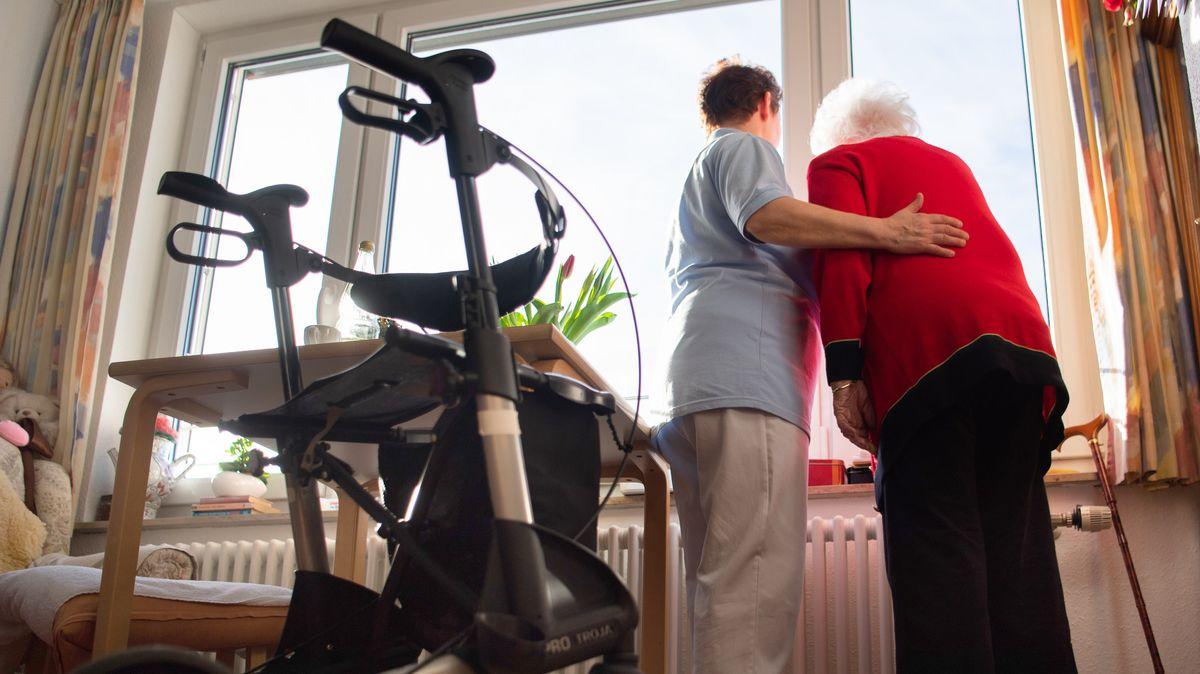 Eine Pflegekraft steht mit der Bewohnerin eines Pflegeheims am Fenster und schaut hinaus, im Vordergrund steht ein Rollator.
