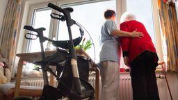 Eine Pflegekraft steht mit der Bewohnerin eines Pflegeheims am Fenster und schaut hinaus, im Vordergrund steht ein Rollator. | Bild:dpa-Bildfunk/Tom Weller