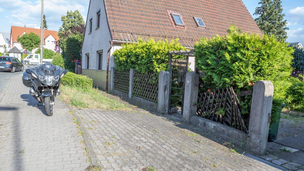 Das beschädigte Motorrad steht vor dem ebenfalls beschädigten Gartenzaun