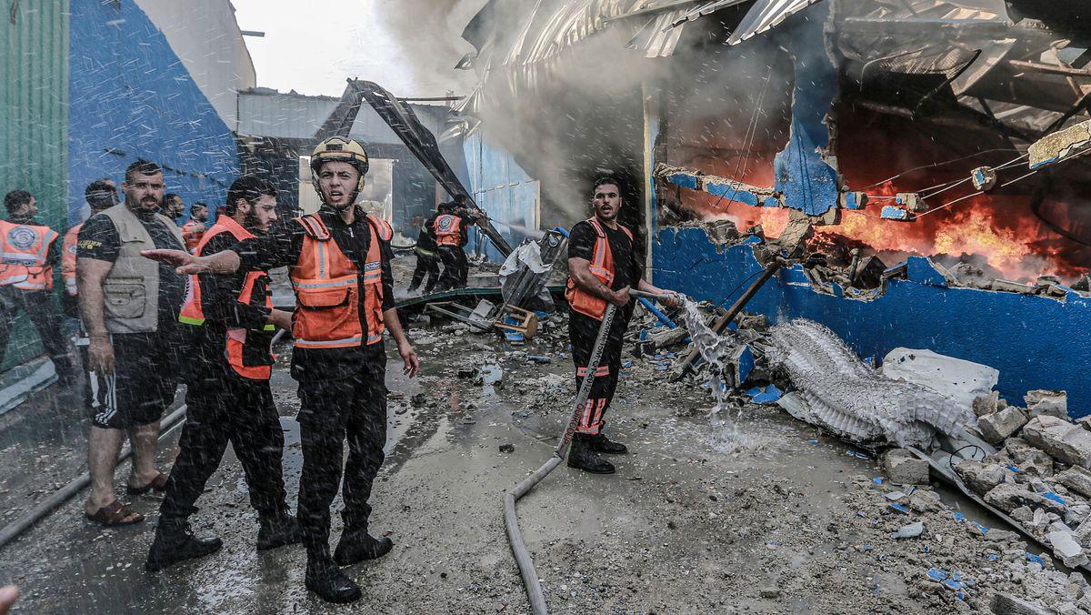 Mitglieder der palästinensischen Zivilverteidigung versuchen nach einem Granateinschlag ein Feuer zu löschen
