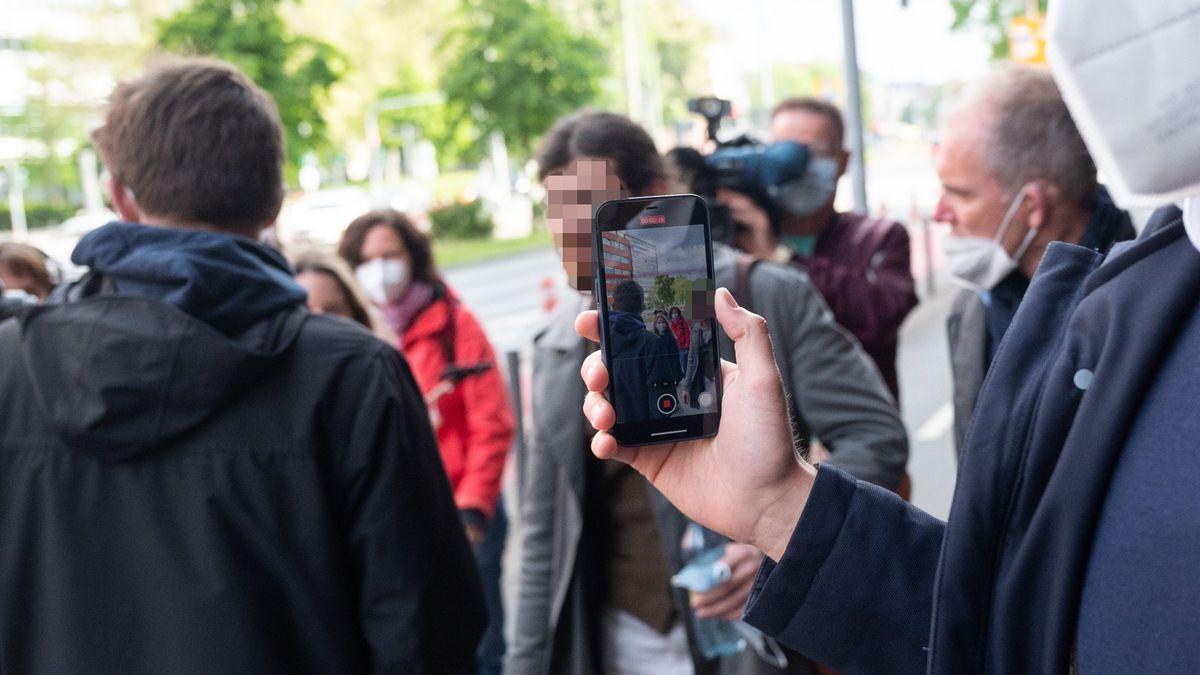 Franco A. (Mitte)  vor Prozessbeginn mit Journalisten.