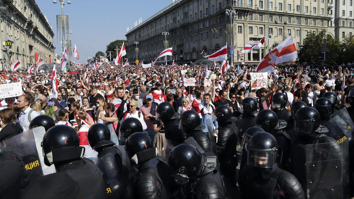 Zahlreiche Polizisten stehen vor einer großen Menge Demonstranten in Minsk, Belarus