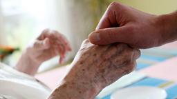 Frau hält die Hand einer Patientin | Bild:dpa-Bildfunk
