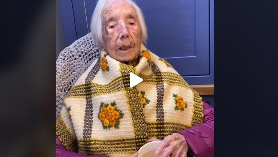 Die 110 Jahre alte Amy Hawkins sitzt in einem Lehnstuhl und hält eine Teetasse in den Händen.