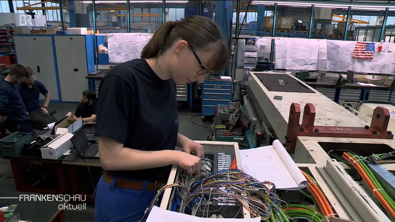 Eine Frau steht in einer Fabrik und arbeitet an einem elektronischen Gerät.