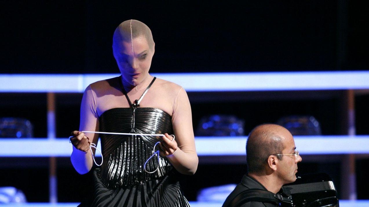 Eine Sängerin steht auf der Bühne und trägt ein Strumpfmaske. In der Hand hält sie ein Seil.