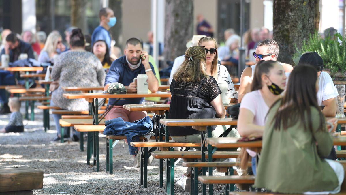Menschen sitze in München in einem Biergarten