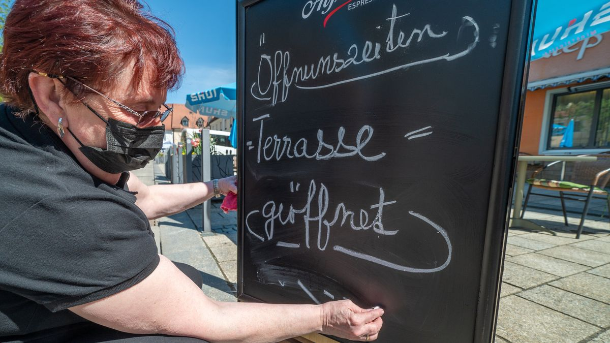 Eine Frau beschriftet die Tafel eines Lokals.