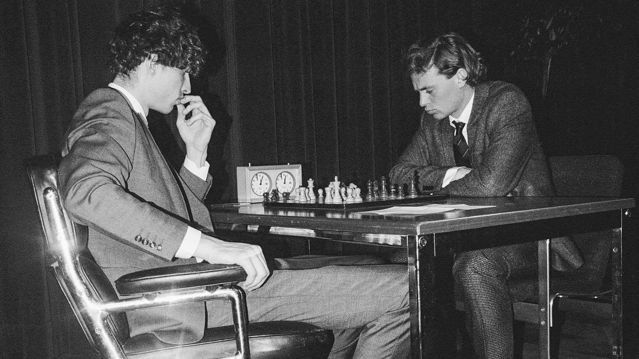 Zwei Männer sitzen sich beim Schach gegenüber. Sie blicken konzentriert auf das Spiel.
