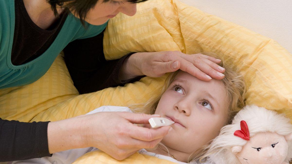 Ein krankes Mädchen liegt im Bett. Die Mutter misst Fieber.
