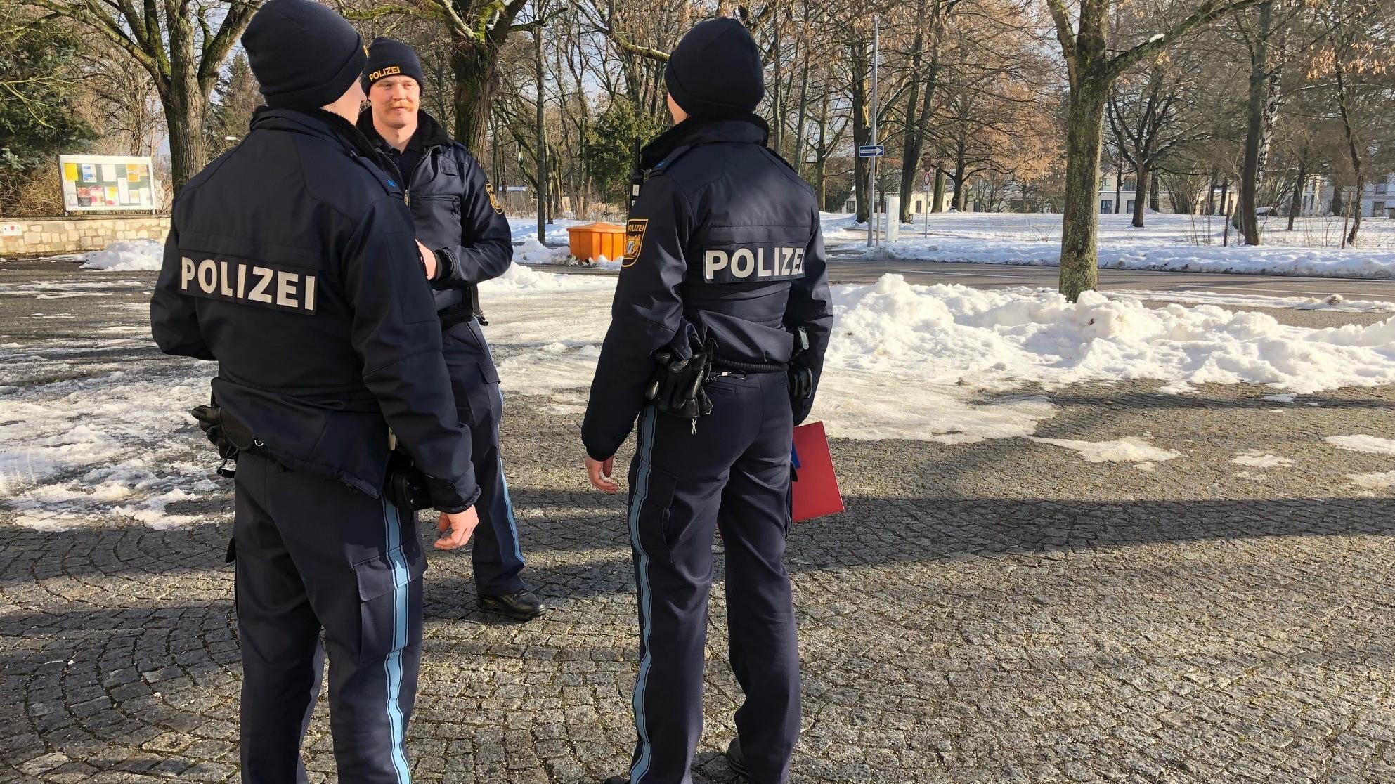 Beamte der Polizei sind mit Bildern aus einem Video unterwegs, um Anwohner zu befragen