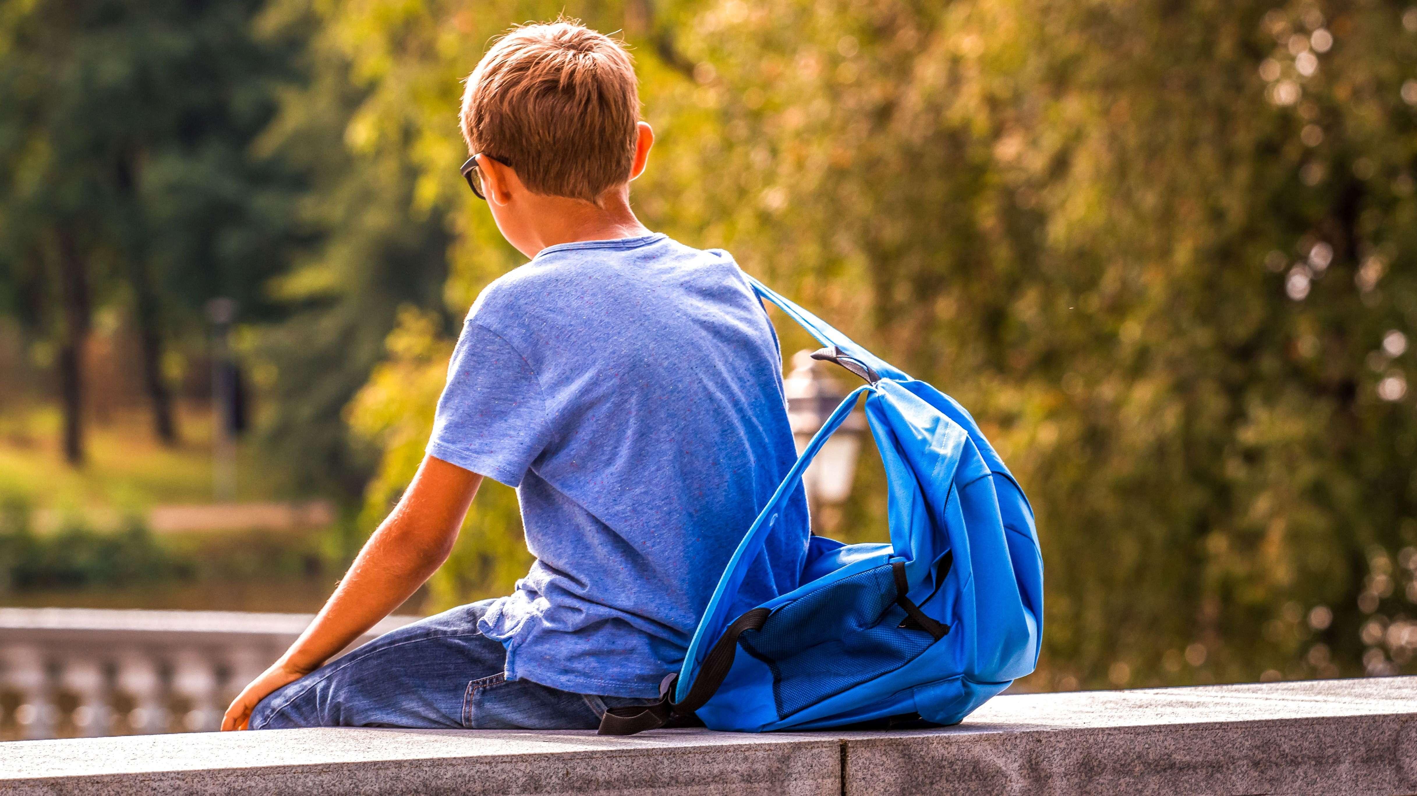 Ein Junge sitzt allein auf einer Mauer. Menschen mit einer Autismus-Spektrum-Störung ziehen sich oft zurück.