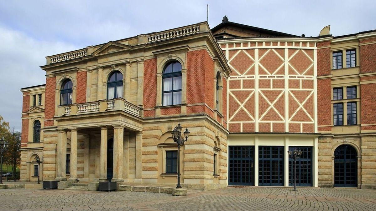 Die rote Backsteinfassade des Bayreuther Festspielhauses mit seinen hohen Fenstern und dem Eingangsportal mit Säulen.