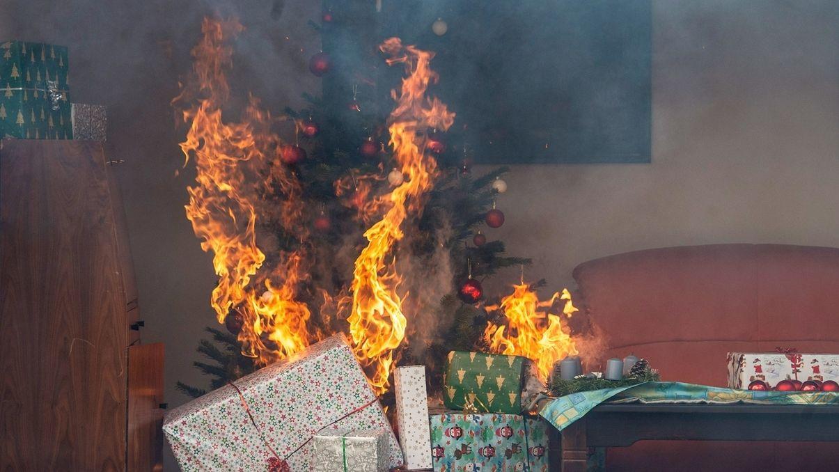 Brennender Christbaum mit Geschenken.