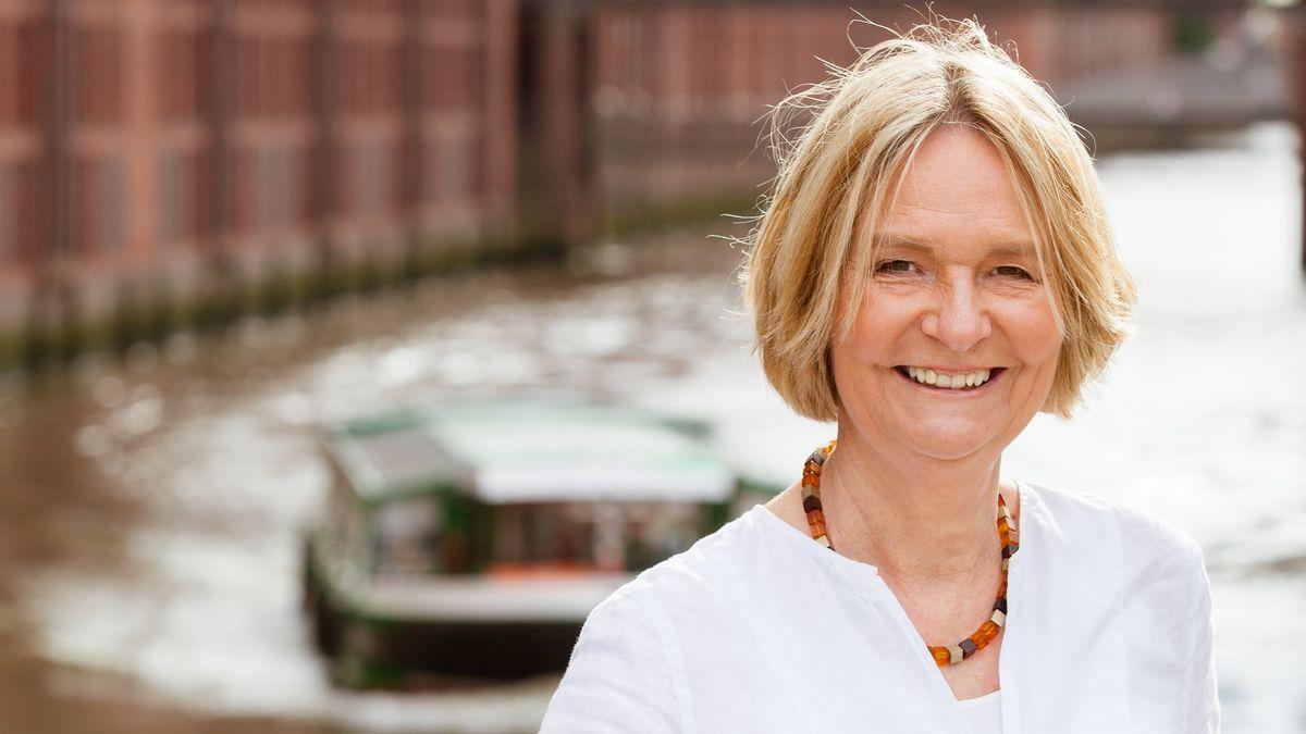 Die Hamburger Schriftstellerin Kirsten Boie steht auf einer Brücke in ihrer Heimatstadt und strahlt in die Kamera