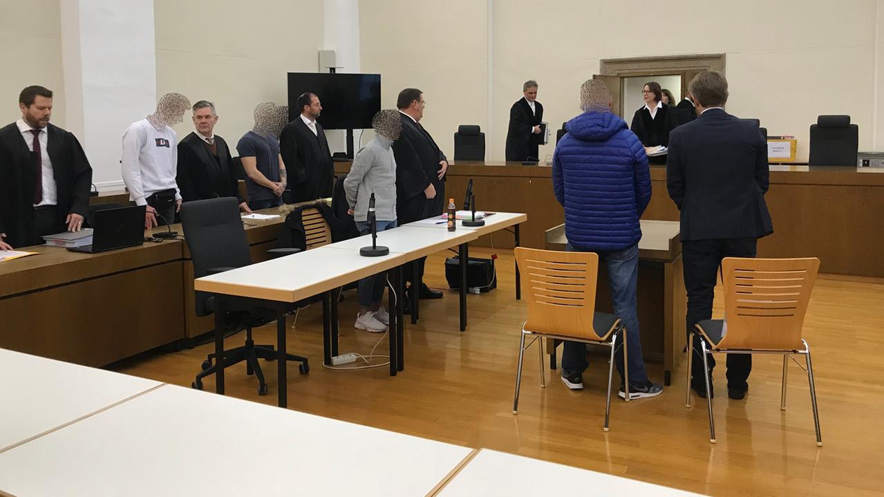 Die Angeklagten warten zusammen mit ihren Anwälten im Gerichtssaal auf die Plädoyers