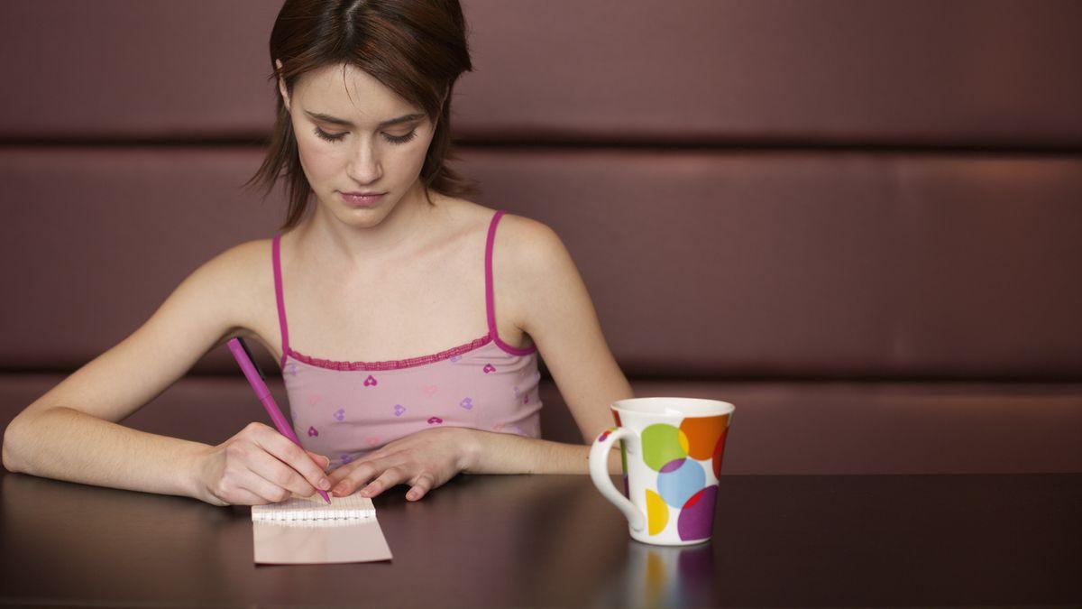 Junge Frau schreibt etwas auf