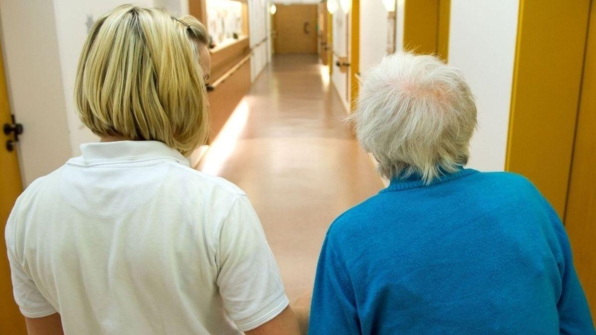 Eine Pflegerin führt eine Seniorin über den Gang eines Heimes.