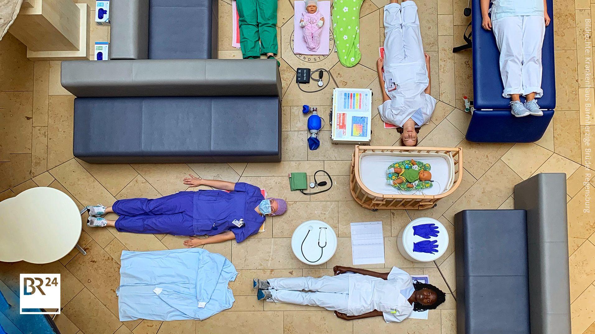 """fünf Frauen, die auf dem Boden liegen. Drei Babypuppen. Ein Stillkissen, ein Stethoskop und etliche andere medizinische Instrumente. Und der kurze Text """"Wir wünschen euch einen schönen Sonntag! ☀️"""" sowie der Hashtag #TetrisChallenge"""