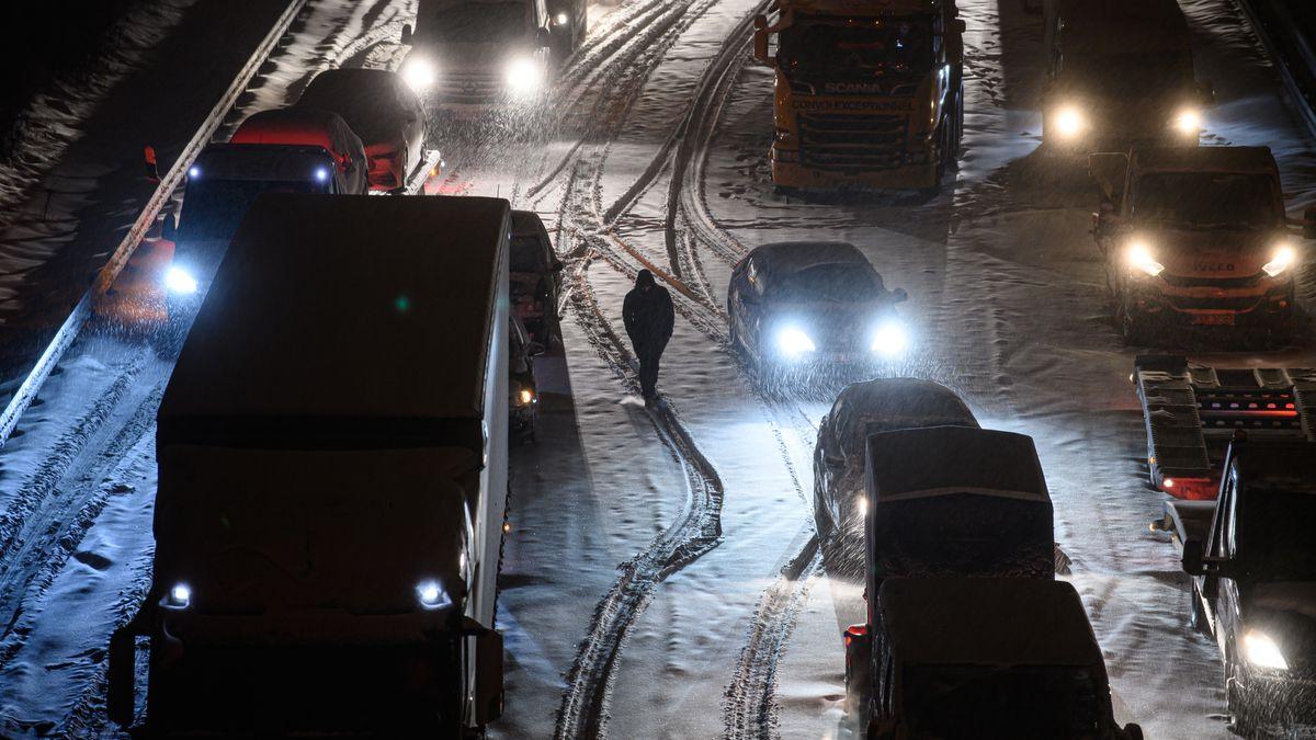 Autos und Lastwagen stehen am frühen Morgen bei Schneefall auf der verschneiten Autobahn 4 bei Dresden im Stau.