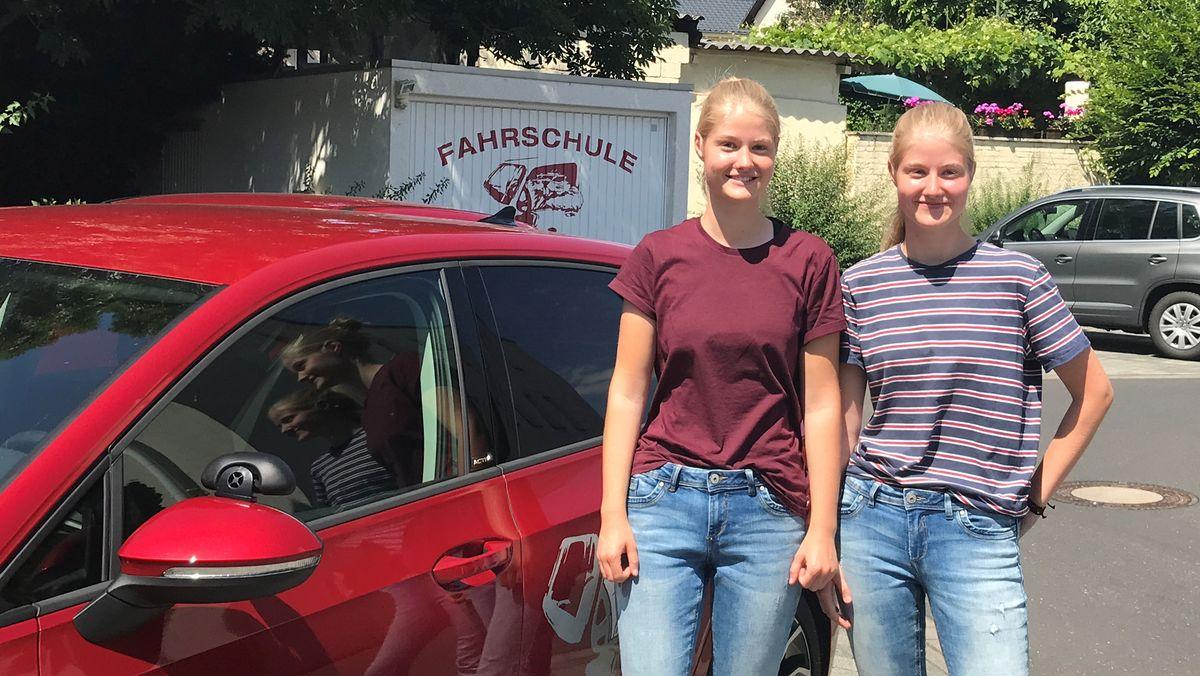 Zwei Mädchen (Zwillinge) stehen neben einem Fahrschulauto