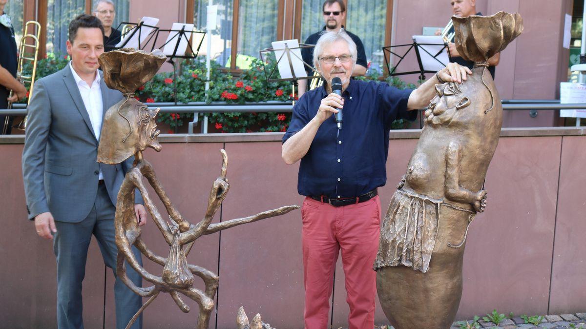"""Lohrs Bürgermeister Mario Paul (l.) und Künstler Roland Schaller enthüllen die """"Mopper und Schnüdel""""-Skulptur."""