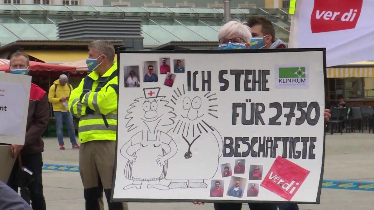 Streikende halten ein Plakat hoch