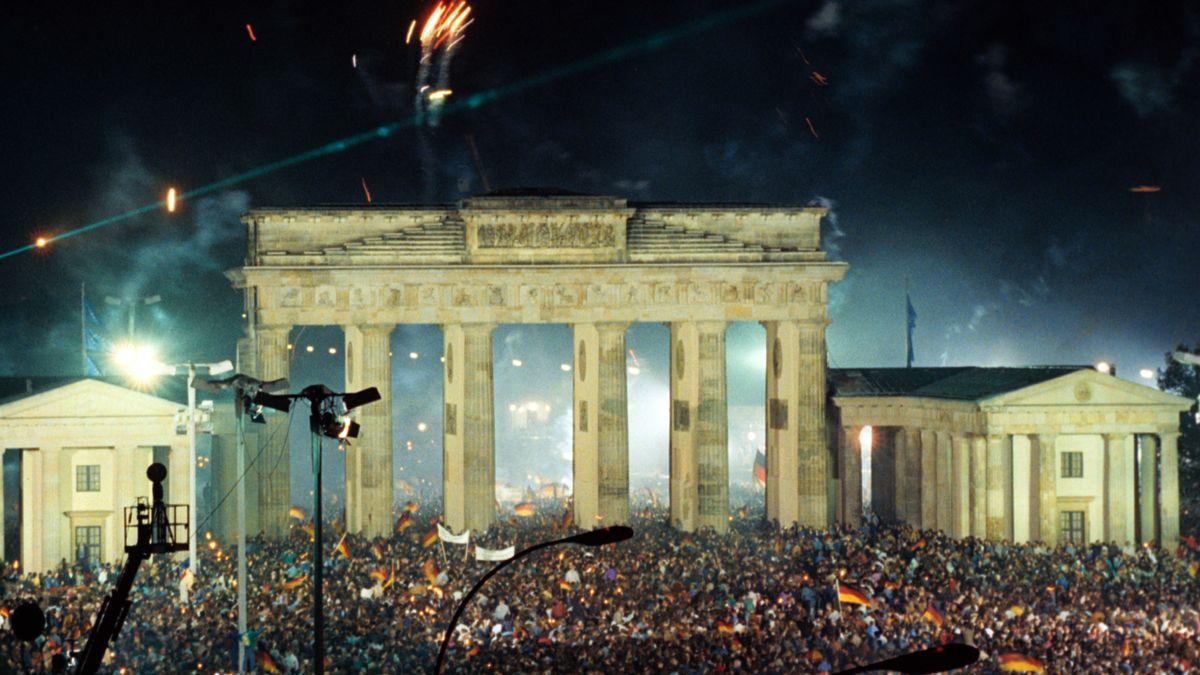 Historische Aufnahme vom Brandenburger Tor in Berlin. Der Platz ist voll mit Menschen, die die Wiedervereinigung feiern.
