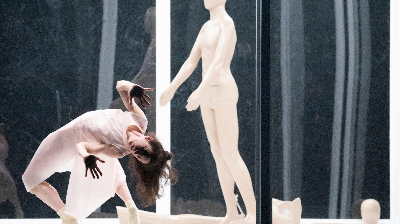 Eine Frau krümmt sich hinter einer Glasscheibe, hinter ihr eine Schaufensterpuppe