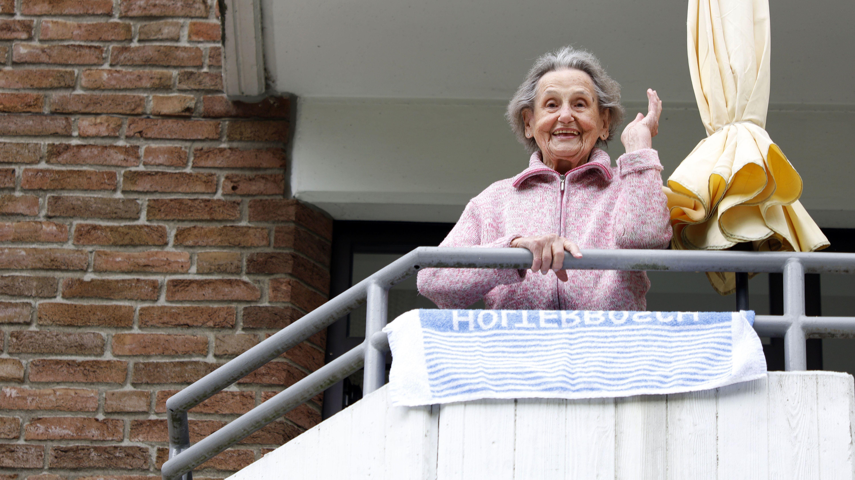 Eine Seniorin steht auf dem Balkon ihres Altenheimzimmers und spricht mit ihren Angehörigen