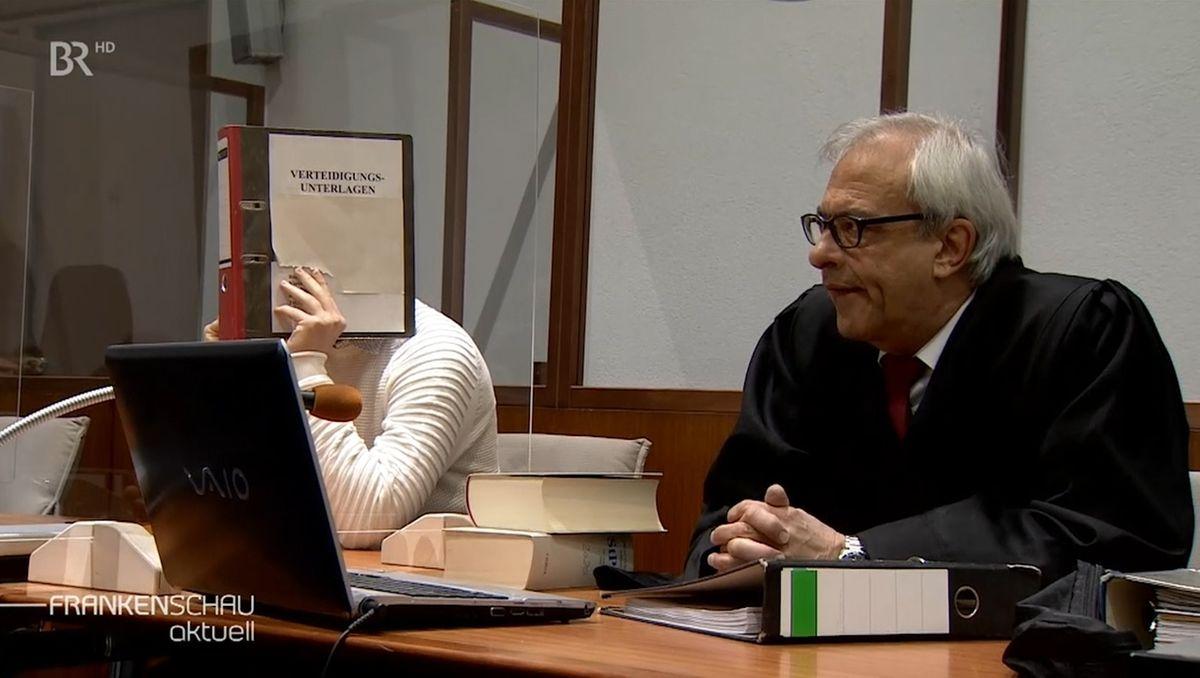 Der Angeklagte verdeckt im Gerichtssaal sein Gesicht mit einem Ordner, neben ihm sitzt sein Anwalt.