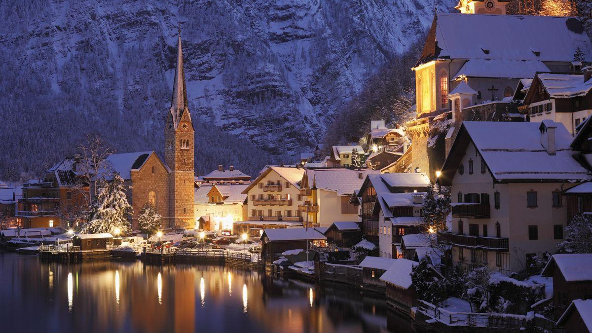 Das winterlich verschneite Hallstatt vom Ufer aus betrachtet, mit Blick auf Kirche und Häuser