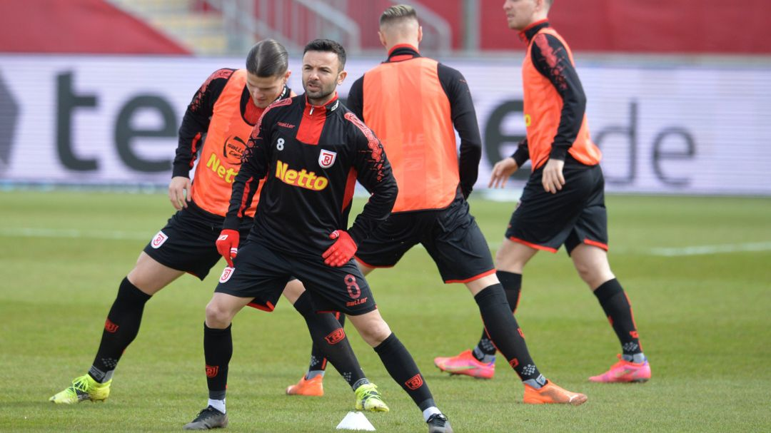 Die Regensburger Spieler um Albion Vrenezi wärmen sich auf.