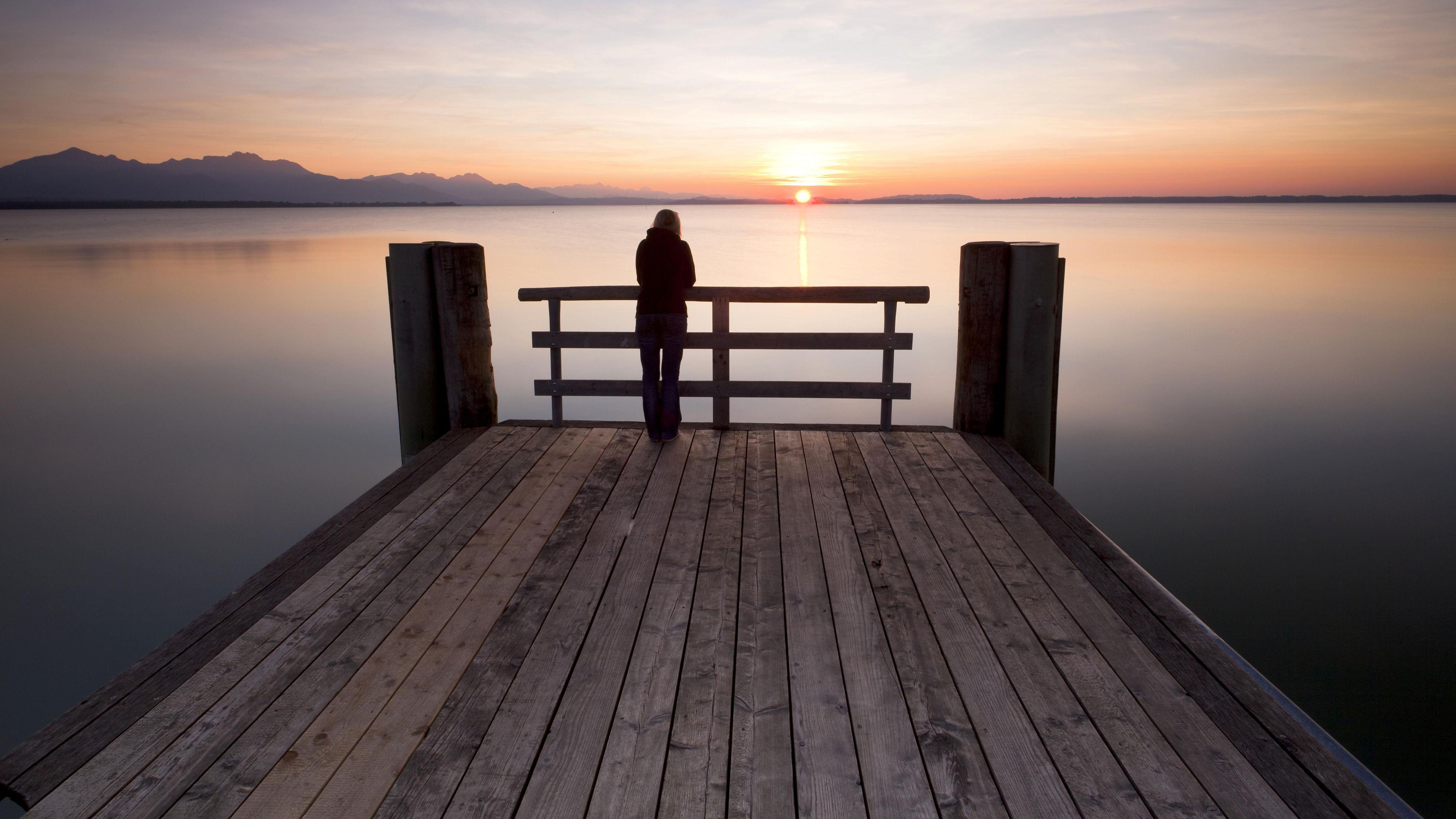 Frau steht alleine an einem Steg und betrachtet den Sonnenuntergang