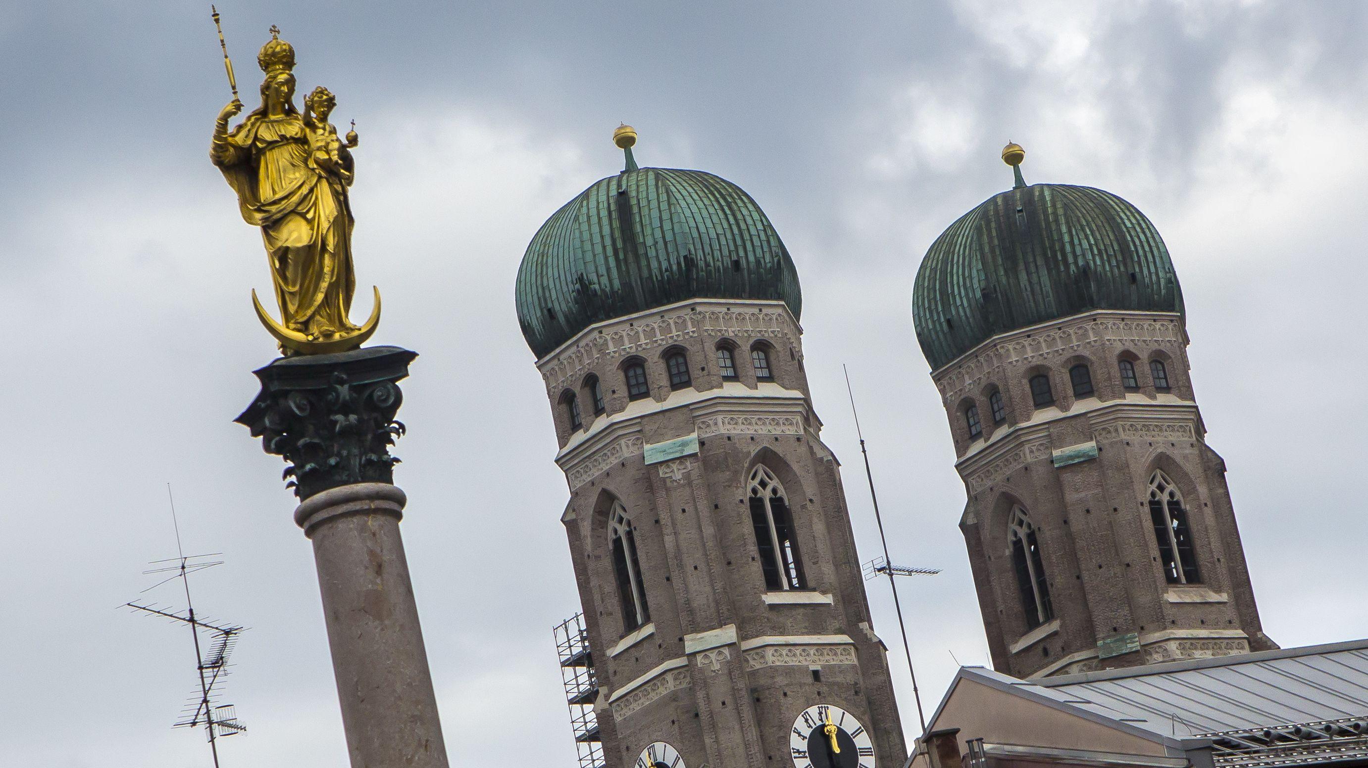 Türme der Münchner Frauenkirche mit Mariensäule im Vordergrund.